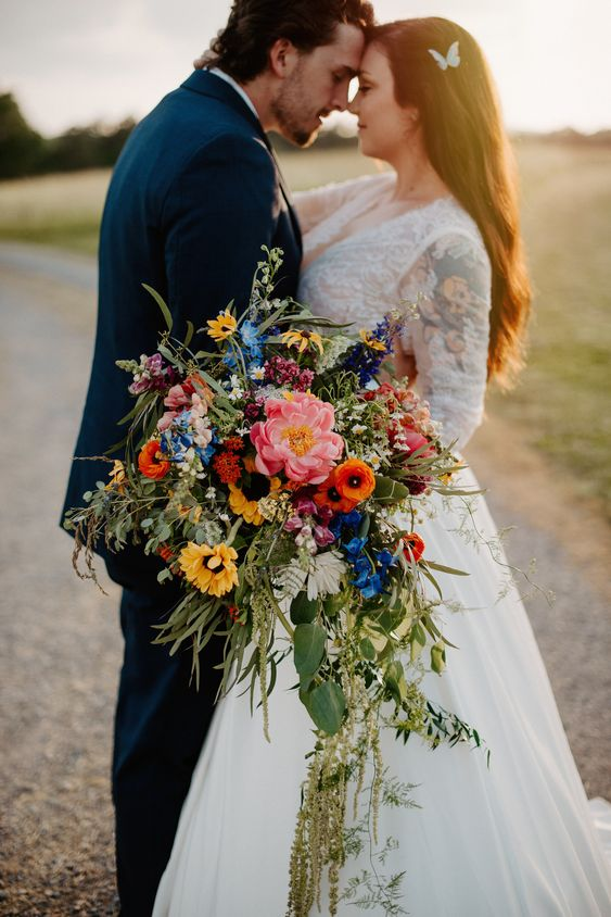 a bright cascading wedding bouquet with pink, orange, yellow and blue blooms and greenery is amazing for summer