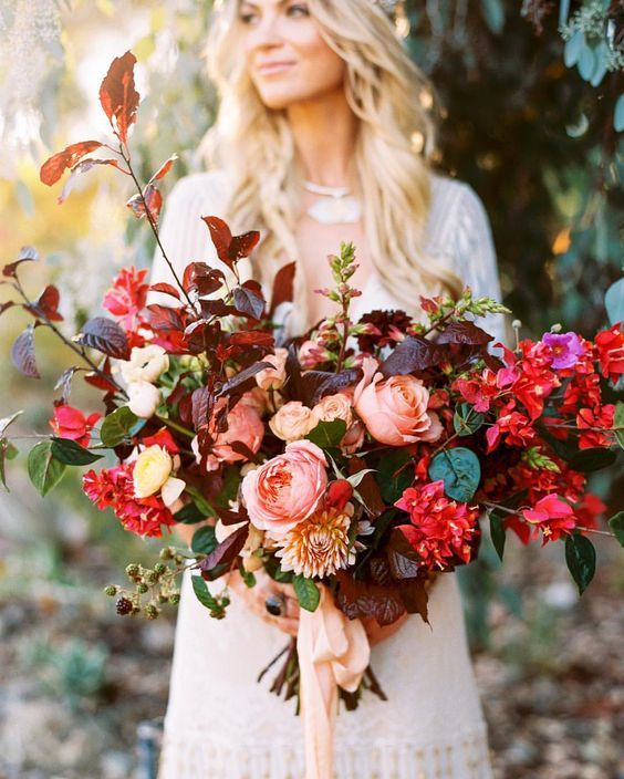 a bright fall wedding bouquet with red, blush and neutral blooms, usual and dark foliage is very bold and cool