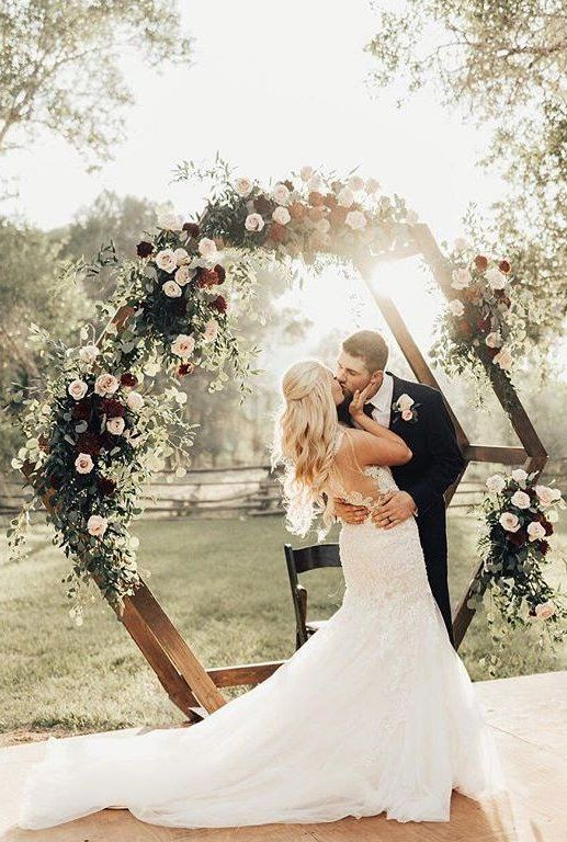 a bright floral wedding arch decorated with greenery, blush and burgundy flowers for an elegant summer wedding