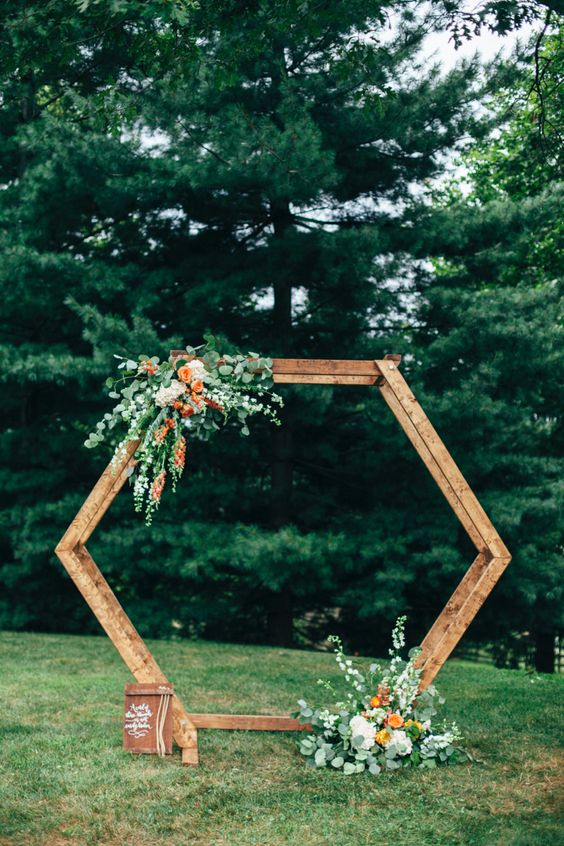 a bright hexagon wedding arch decorated with greenery, white and orange blooms for a bold summer or fall wedding