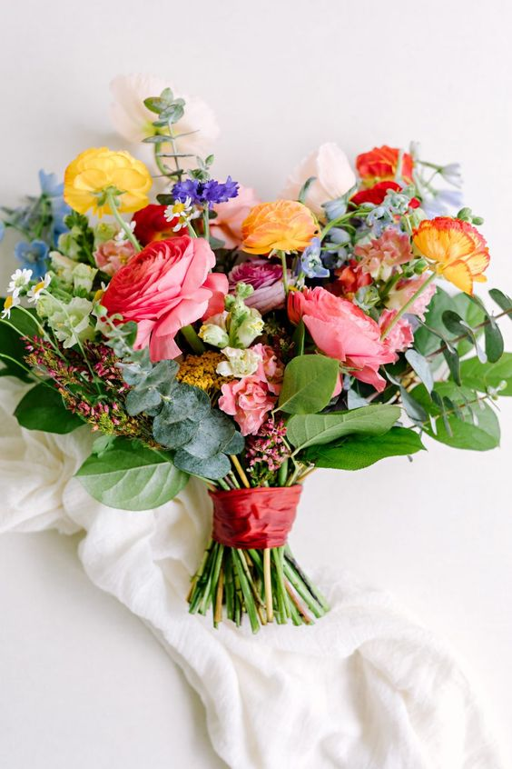 a bright summer wedding bouquet with pink, yellow, purple and blue flowers and greenery for a refined summer wedding