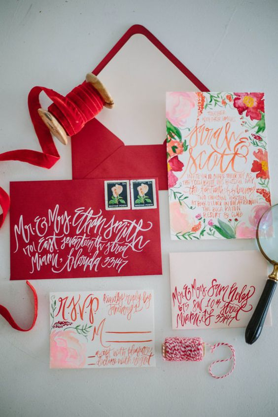 a bright summer wedding invitation suite with deep red envelopes and floral hand painted invites is gorgeous