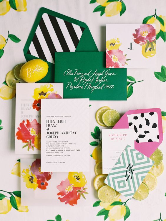 a bright wedding invitation suite with a hot pink and a green envelope, watercolor florals, a chevron piece for a fun look