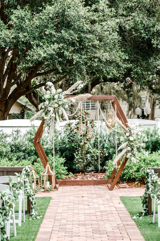 a catchy hex wedding arch ith greenery, white blooms, pampas grass, beaded garlands, candle lanterns hanging for a spring wedding