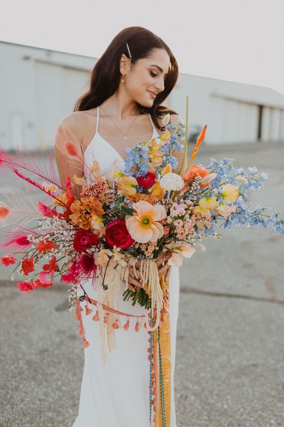 a cheerful wedding bouquet with orange,red, yellow and blue blooms, colorful feathers and tassels and fringe for a boho bride