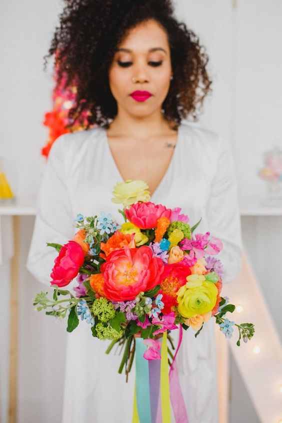 a cheerful wedding bouquet with red, coral, yellow, orange and blue flowers and long colorful ribbons is cool