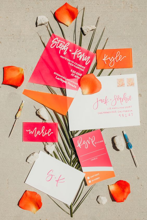 a cheerful wedding invitation suite in hot pink and orange, with pretty calligraphy and sheer parts is wow