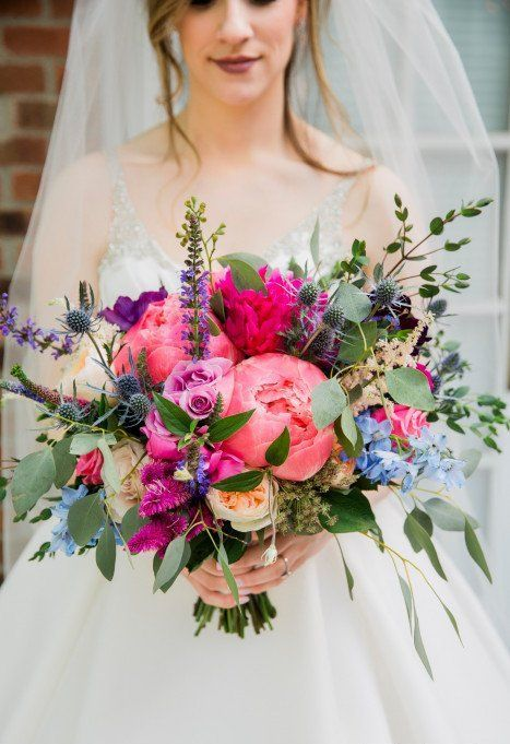 a chic and bright wedding bouquet with pink, hot pink, blue and purple blooms, thistles and foliage is beautiful