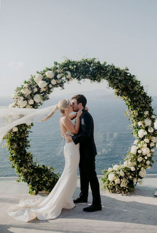 a chic round wedding arch with greenery and white blooms on some parts of it looks stylish and out of the box