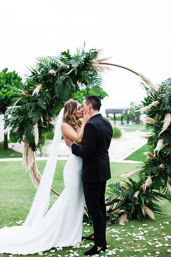 a chic tropical wedding arch covered with pampas grass and fronds is a lovely idea for a boho tropical wedding