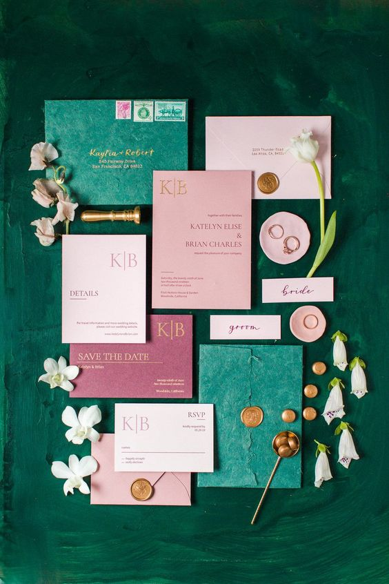 a chic wedding invitation suite wiht emerald envelopes, pink and mauve touches and gold lettering and calligraphy
