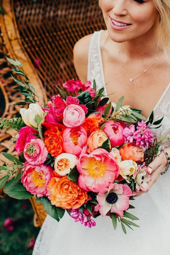 a classy wedding bouquet with pink, orange, light pink and white blooms and greenery for a bright wedding