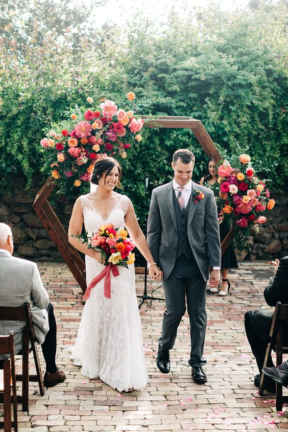 a colorful hex wedding arch with bold pink, red, orange blooms for a colorful summer wedding