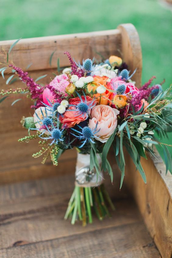 a colorful wedding bouquet with blush, pink, orange and yellow blooms, greenery and thistles is pretty and fun