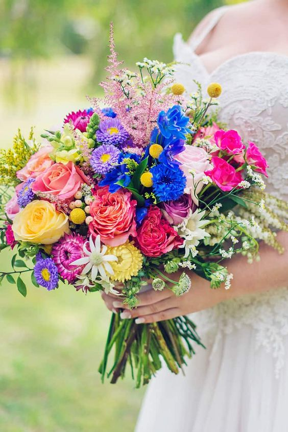 a colorful wedding bouquet with electric blue, yellow, pink, hot pink, purple blooms, astilbe, greenery is amazing