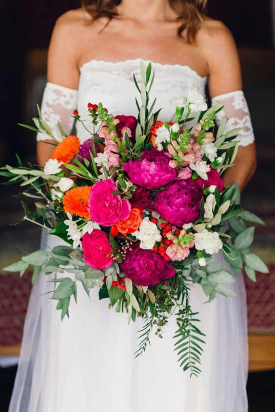 a colorful wedding bouquet with hot pink, orange, pink and white blooms, berries and various types of greenery