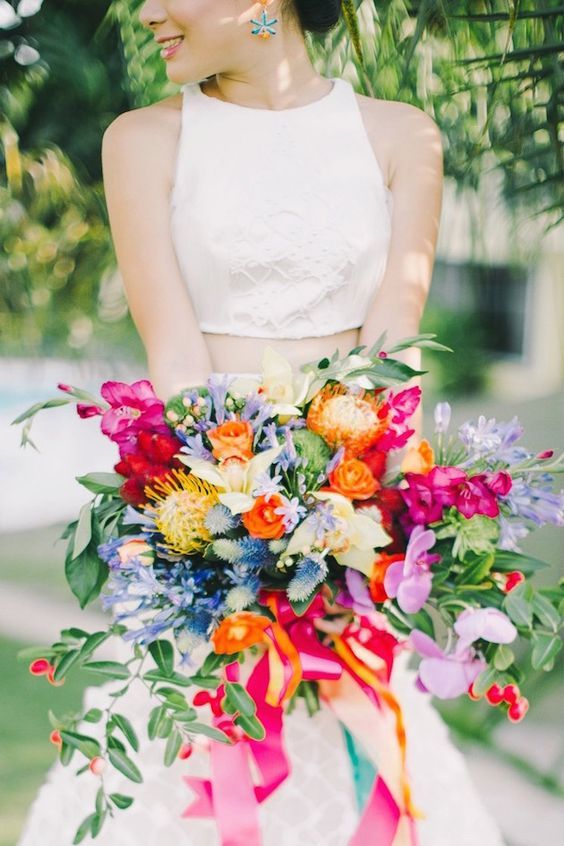 a colorful wedding bouquet with orange, fuchsia, pink, yellow and blue blooms, pincushion proteas and greenery plus colorful ribbons