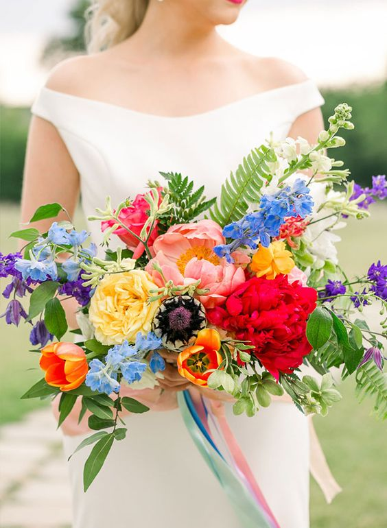 a colorful wedding bouquet with red, blush, yellow, orange, blue and purple blooms, greenery and fern for summer