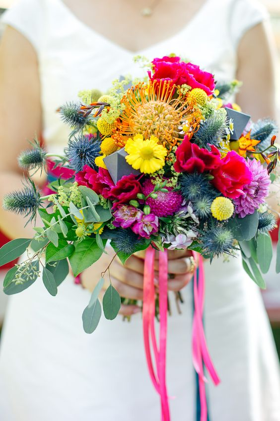 a colorful wedding bouquet with thistles, fuchsia and pink blooms, yellow ones and billy balls plus eucalyptus