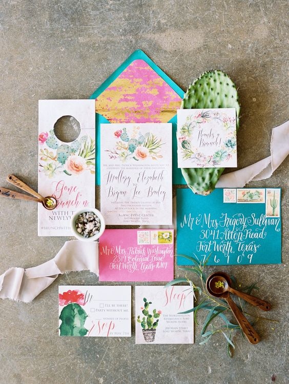 a colorful wedding desert invitation suite with teal and pink envelopes, bold cactus painted and bright calligraphy is wow