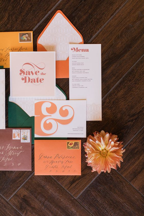a colorful wedding invitation suite with orange envelopes, a green one, bold and colorful printing and letters