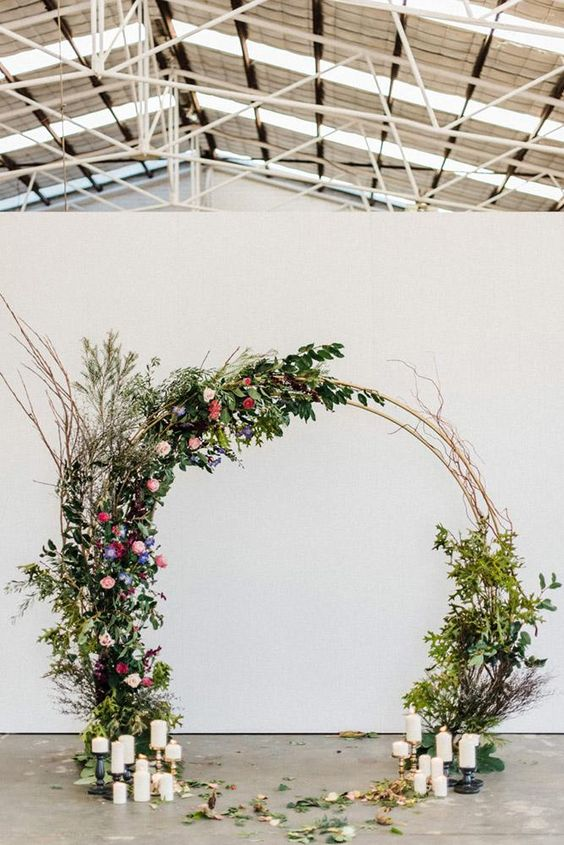 a cool round weddign arch decorated with greenery, pink, lilac and red blooms, twigs and candles o the ground