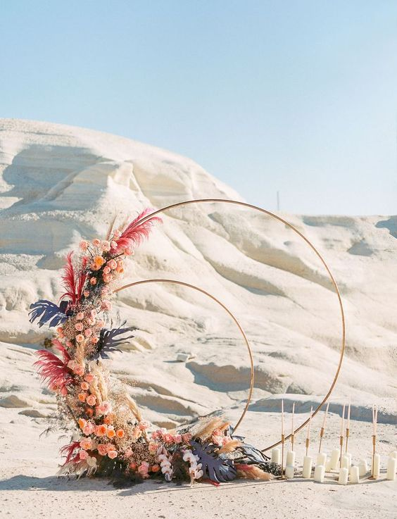 a creative double round wedding arch with pink blooms, colorful pampas grass and fronds for a bold desert wedding