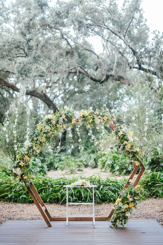 a creative spring hexagon wedding arch decorated with greenery, white and yellow blooms and cascading greenery branches