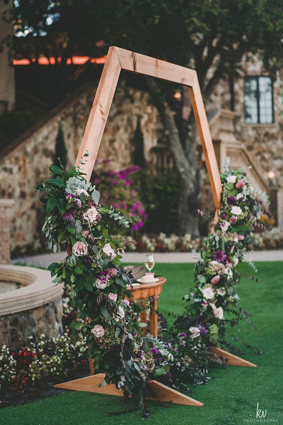 a fantastic hexagon wedding arch decorated with greenery, blush, purple blooms for a summer or fall wedding