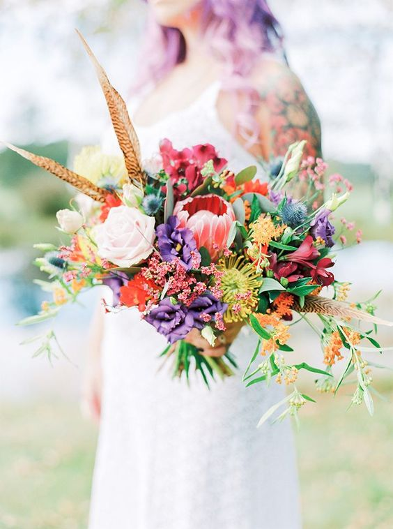 a festival wedding bouquet with blush, red, purple and uellow blooms, berries, feathers and thistles plus a bit of greenery