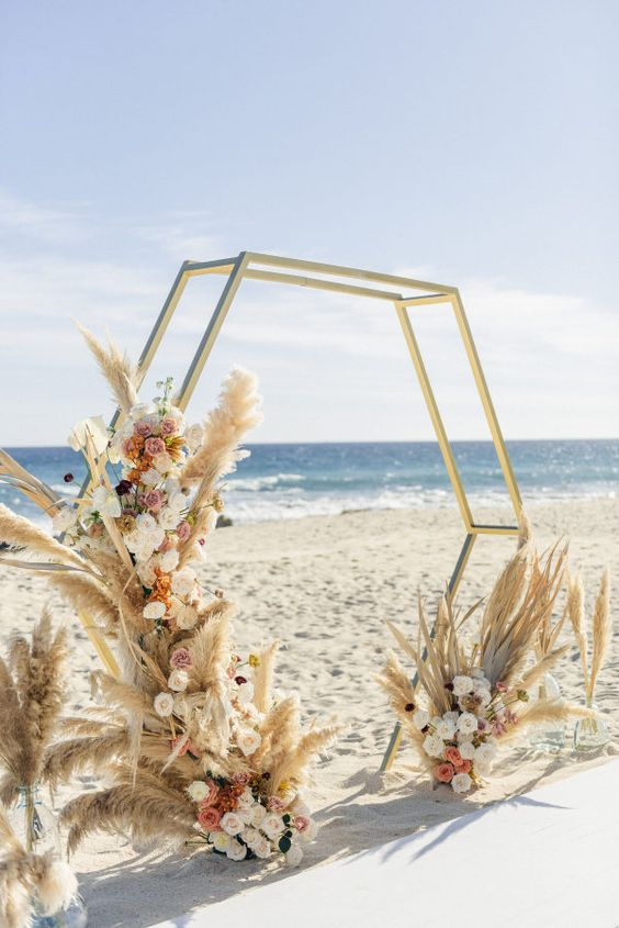 a glam boho hex wedding arch with pampas grass, white, blush and pink blooms is a lovely idea to rock
