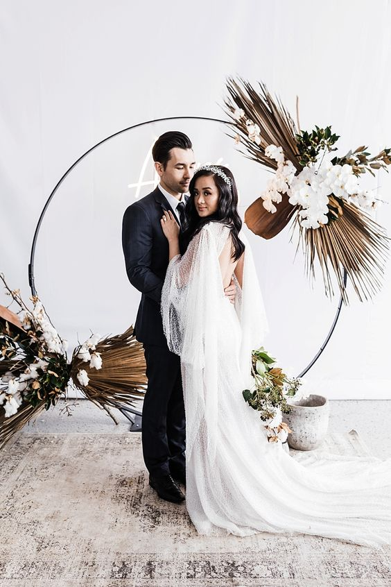 a glam boho wedding arch with dried fronds, white orchids and some foliage is a lovely idea for any wedding