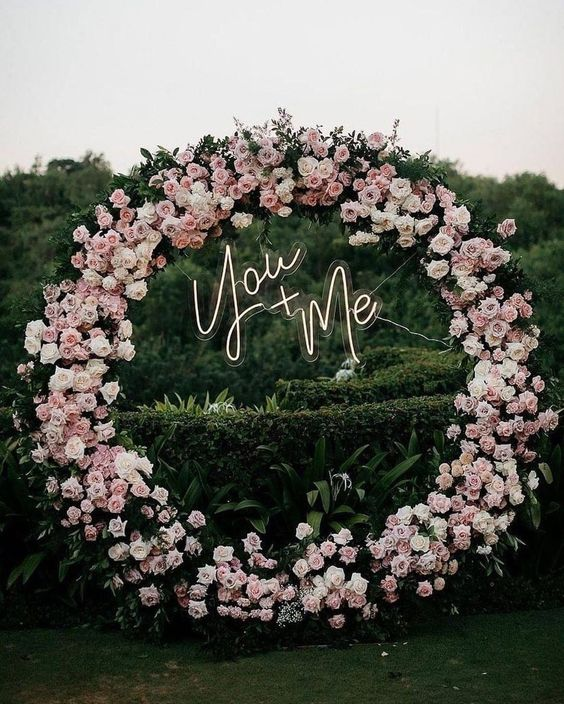 a glam round wedding arch decorated with greenery, light pink and white blooms and a neon sign is chic