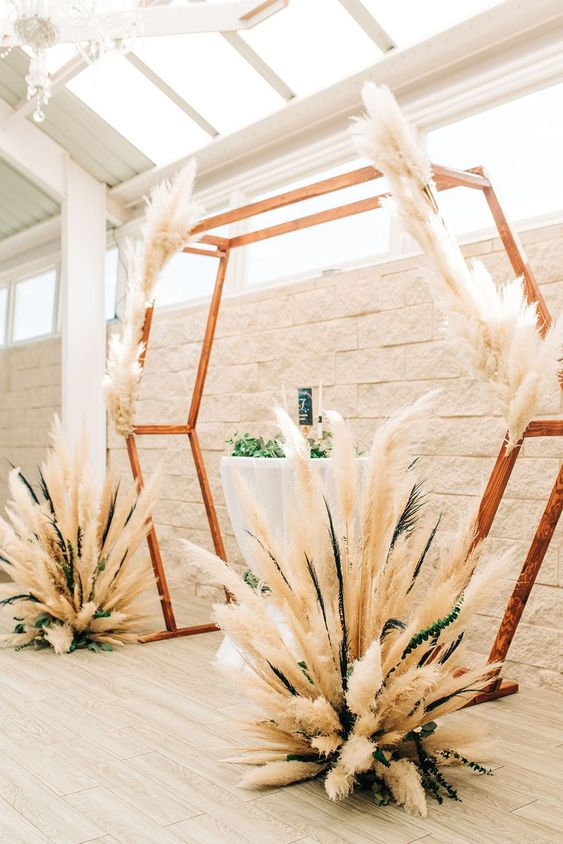 a gorgeous boho hexagon wedding arch decorated with pampas grass and greenery is a lovely idea for a boho wedding