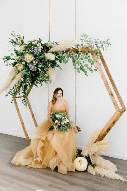 a hex wedding arch with lush greenery, pampas grass, white and blue hydrangeas for a stylish fall wedding