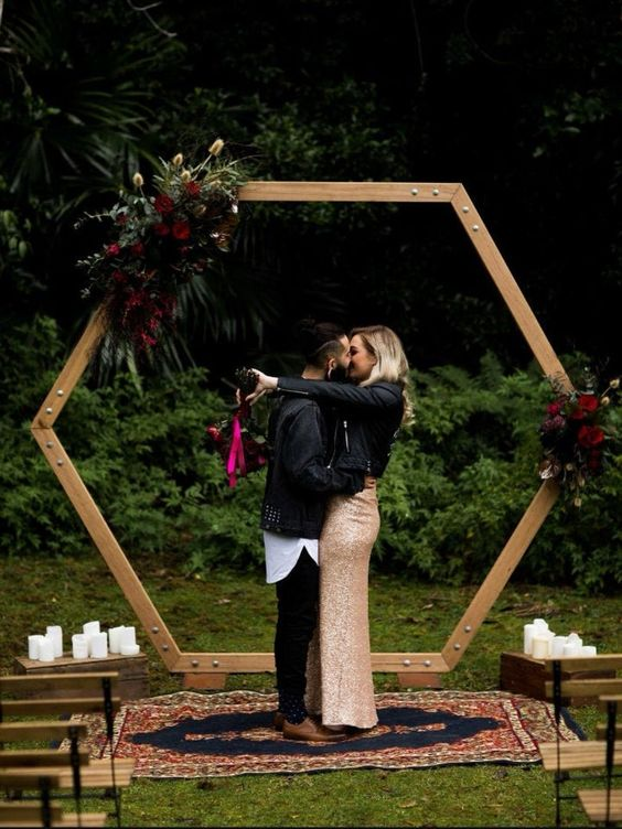 a hexagon wedding arch decorated with greenery, grasses and dark burgundy blooms for a moody fall wedding