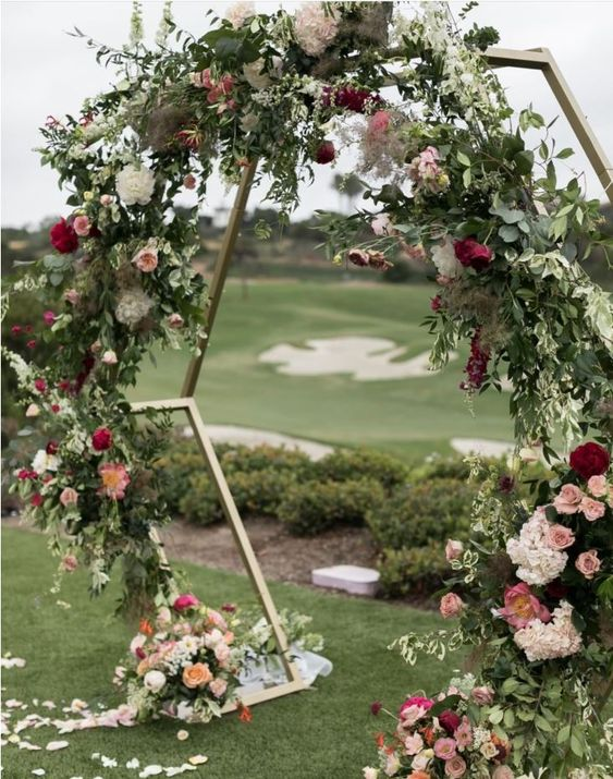 a hexagon wedding arch decorated with lush greenery, pink, peachy, orange and white flowers all over it