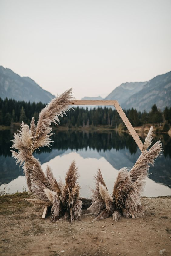 a hexagon wedding arch decorated with pampas grass is a pretty idea for a boho wedding in any season