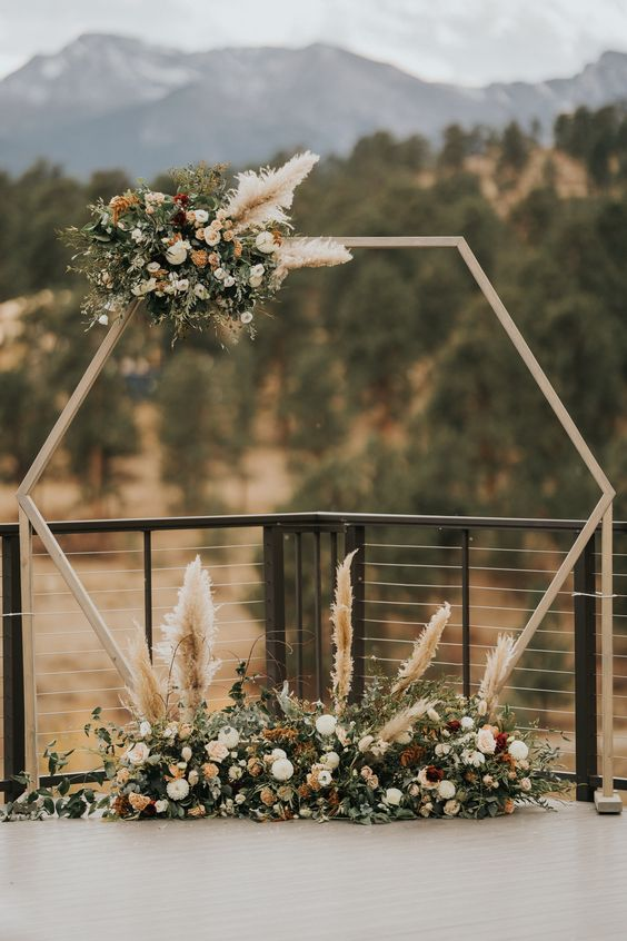 a hexagon wedding arch with a flower and pampas grass arrangement on one corner and a floral arrangement at the base is amazing