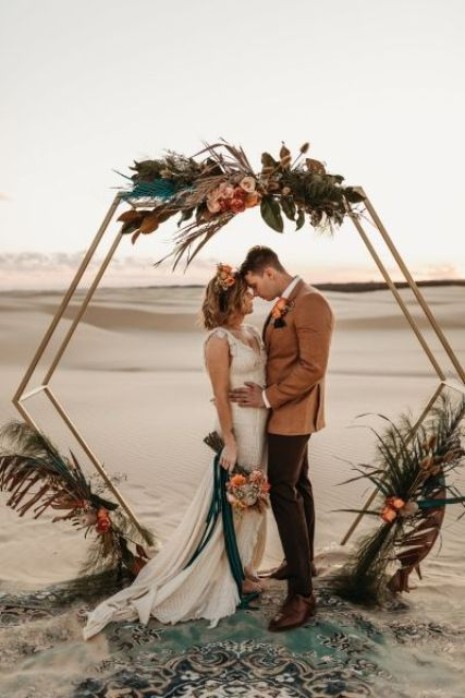 a hexagon wedding arch with blush and rust blooms, dark foliage and grasses and spray painted fronds for a boho wedding
