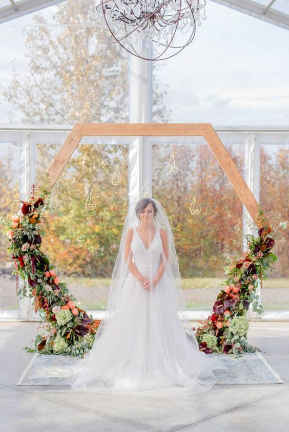 a hexagon wedding arch with greenery and dark and bold flowers and candle lanterns hanging for a fall wedding