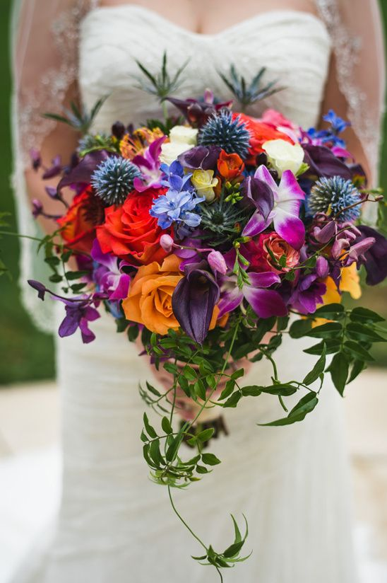 a jewel-tone wedding bouquet with red, yellow, purple and blue flowers, allium, thistles and greenery for a fall wedding