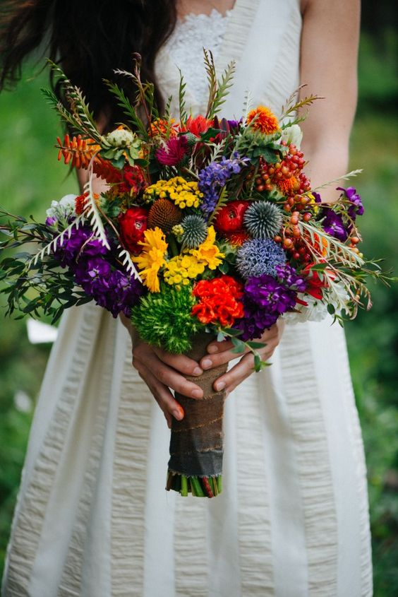 a jewel-tone wedding bouquet with yellow, red, purple flowers, allium, greenery, foliage for a cheerful wedding in summer or fall