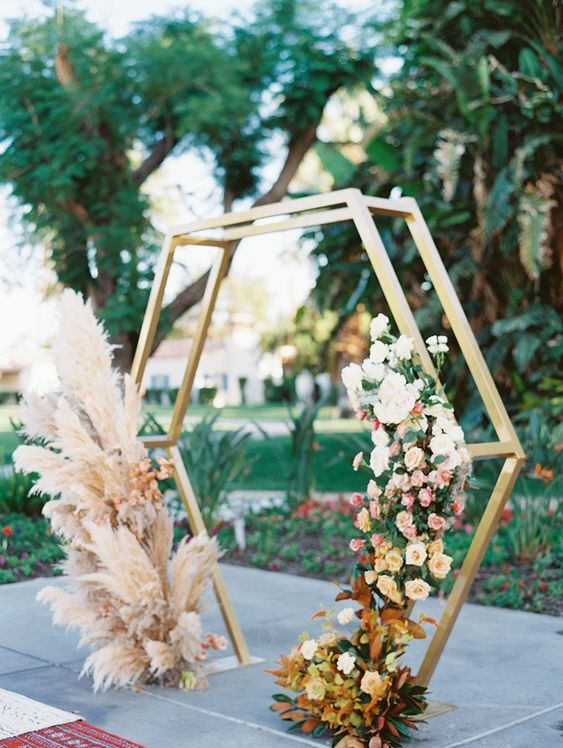 a lovely hexagon wedding arch with blush pampas grass, blush and white blooms and bold foliage for a boho wedding