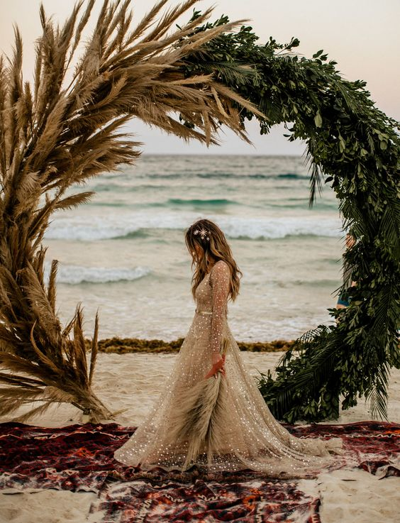a lovely tropical round wedding arch decorated with pampas grass and greenery is a gorgeous idea for a beach wedding