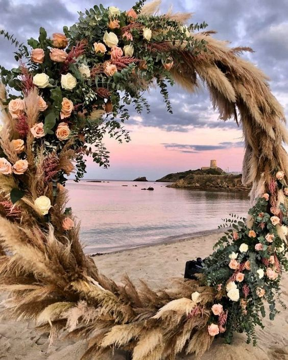 a lush and bold round wedding arch covered with pampas grass, eucalyptus, blush, pink and white roses for a seaside wedding