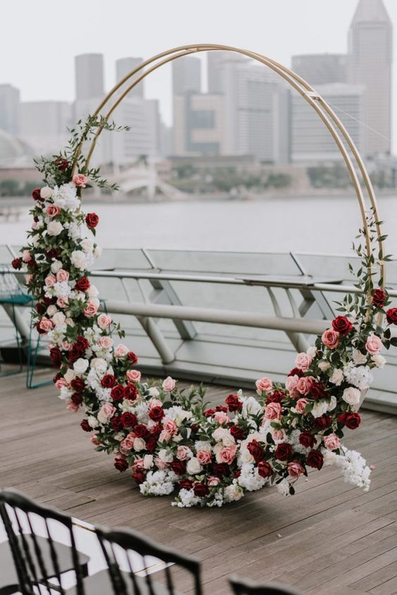 a lush round wedding arch decorated with red, white and pink blooms and some greenery is a lovely idea