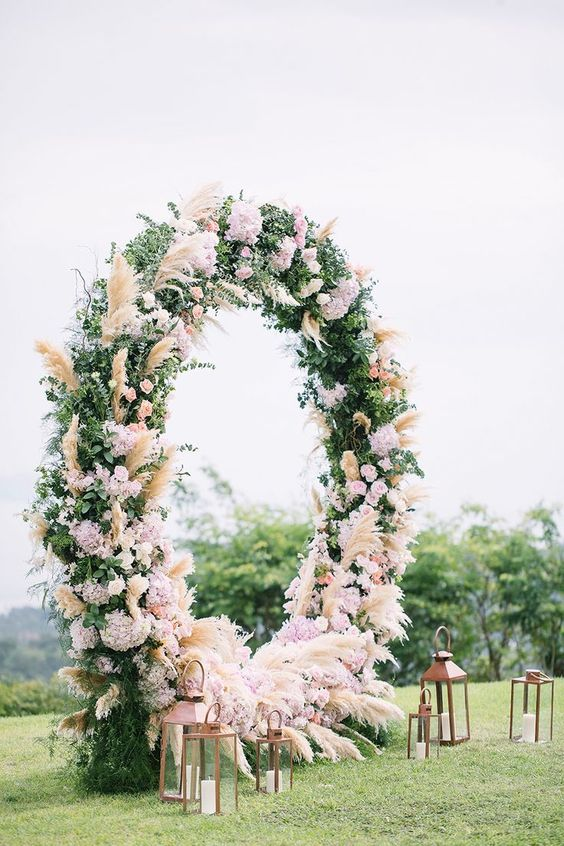 a luxurious round wedding arch with greenery, pampas grass and pink and blush blooms and candle lanterns is chic