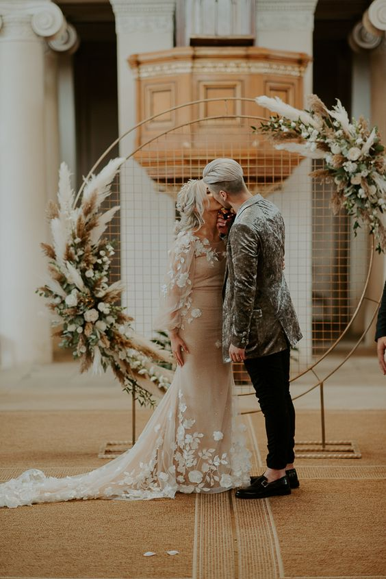 a modern boho round wedding arch with pampas grass, white blooms and greenery and mesh in the arch