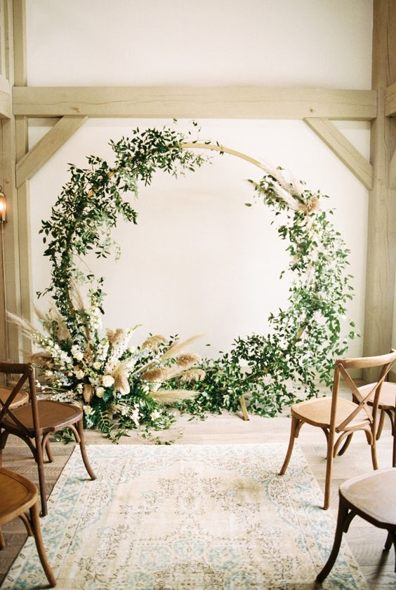a modern meets organic wedding arch with greenery and pampas grass is a very beautiful and chic idea